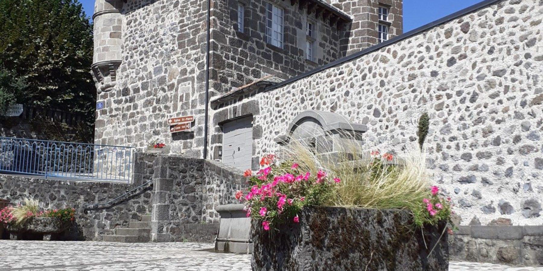 Surplombant la place principale du village, la Maison du Chevalier des Huttes (Auvergne, France) à Vic sur Cère crée le lien urbain à un séjour de découverte du Cantal, de son terroir et de sa nature préservée.